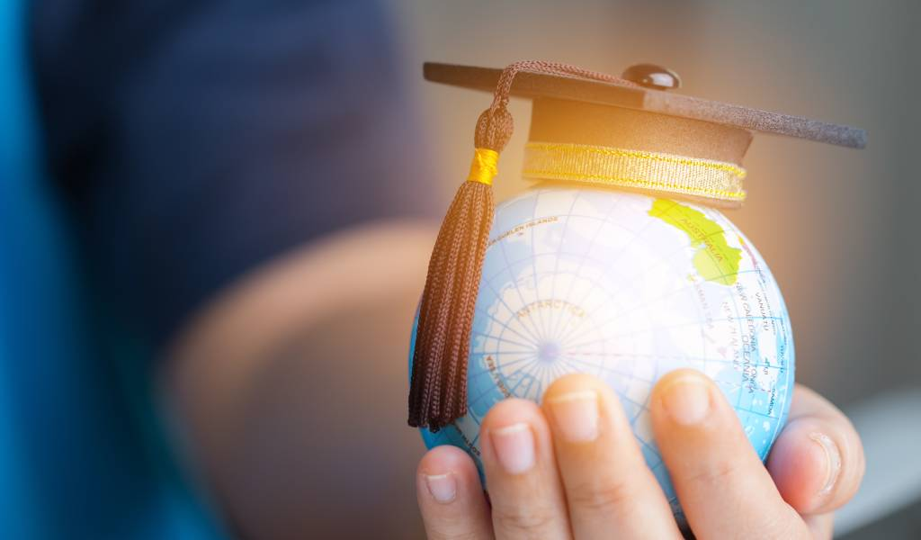 A globe with a graduation cap in a women's hand.